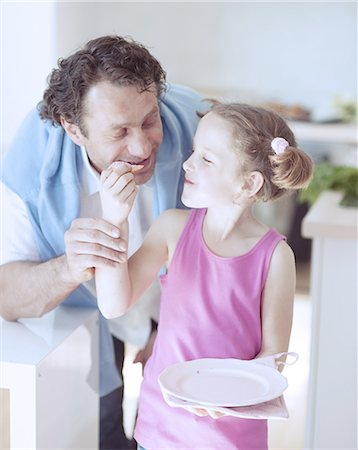 Young girl feeding her father Stock Photo - Premium Royalty-Free, Code: 693-06967464