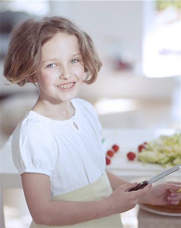 preteen girls faces photo - Young girl holding knife in kitchen Stock Photo - Premium Royalty-Free, Code: 693-06967468