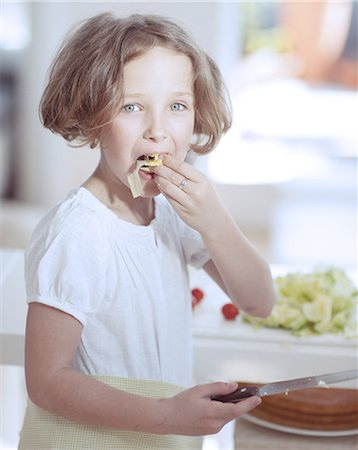 preteen girls faces photo - Young girl eating salad whilst holding knife in kitchen Stock Photo - Premium Royalty-Free, Code: 693-06967469