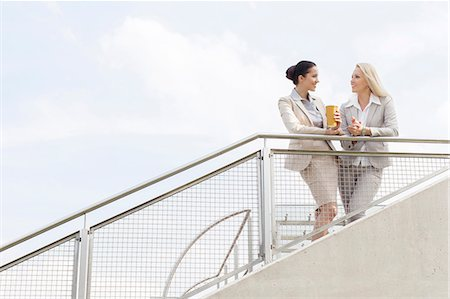 Low angle view of young businesswomen talking while standing by railing against sky Stock Photo - Premium Royalty-Free, Code: 693-07444456