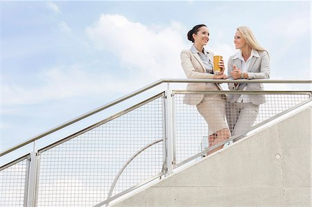 Low angle view of happy businesswomen discussing while standing by railing against sky Stock Photo - Premium Royalty-Free, Code: 693-07444457