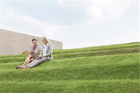 staff - Full length of female business executives with disposable coffee cup and laptop sitting on grass steps against sky Stock Photo - Premium Royalty-Free, Code: 693-07444459