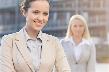 staff - Portrait of happy young businesswoman with female colleague in background Stock Photo - Premium Royalty-Free, Code: 693-07444466