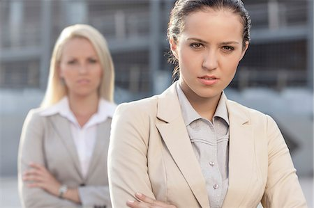 staff - Portrait of serious young businesswoman with female colleague in background Stock Photo - Premium Royalty-Free, Code: 693-07444467