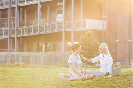 Young businesswomen discussing in office lawn Stock Photo - Premium Royalty-Free, Code: 693-07444471