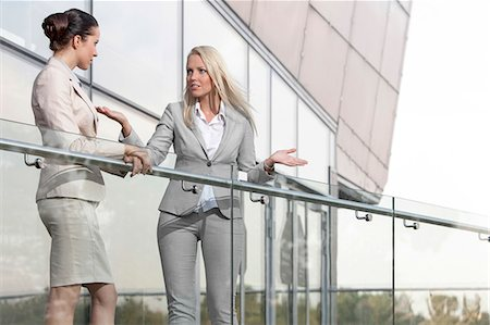 Young businesswoman arguing with female colleague at office balcony Stock Photo - Premium Royalty-Free, Code: 693-07444473