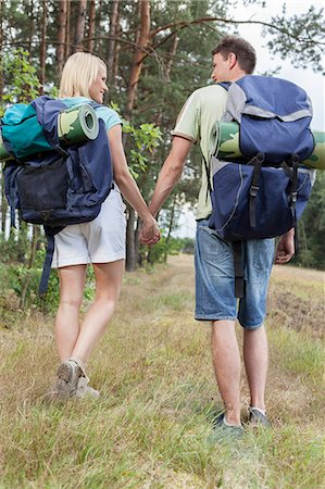 Full length rear view of young backpackers holding hands in countryside Stock Photo - Premium Royalty-Free, Code: 693-07444492