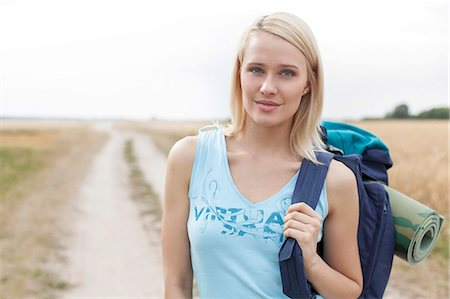 Portrait of beautiful female hiker with backpack standing on field Stock Photo - Premium Royalty-Free, Code: 693-07444514
