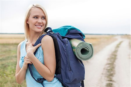 Beautiful woman with backpack looking away while hiking at field Stock Photo - Premium Royalty-Free, Code: 693-07444515