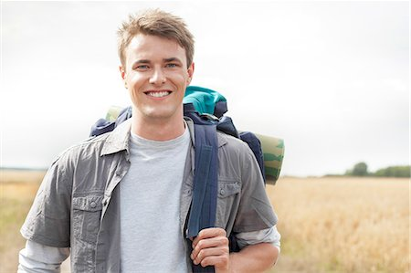 Portrait of handsome male hiker with backpack standing on field Stock Photo - Premium Royalty-Free, Code: 693-07444513