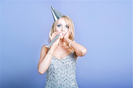 Sexy blonde party girl wearing silver dress and blowing party whistle Stock Photo - Premium Royalty-Free, Code: 693-07444529