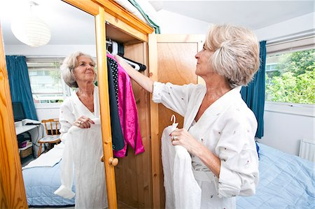 Senior woman selecting dress from closet at home Stock Photo - Premium Royalty-Free, Code: 693-07444521