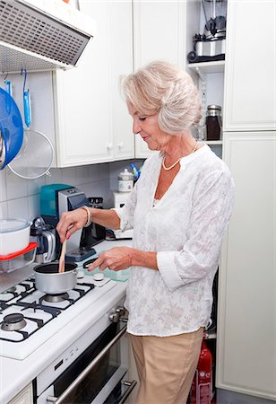 domestic life - Senior woman cooking at kitchen counter Stock Photo - Premium Royalty-Free, Code: 693-07444522