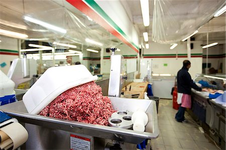 Minced meat in container with employee standing in background at store Stock Photo - Premium Royalty-Free, Code: 693-07444546