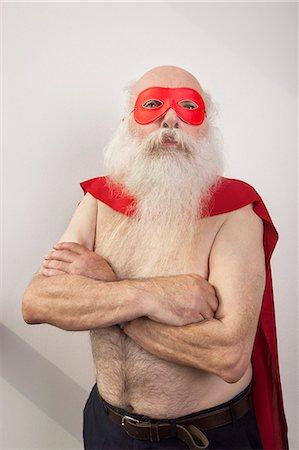 Shirtless senior man in super hero costume against white background Stock Photo - Premium Royalty-Free, Code: 693-07455846