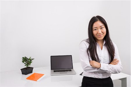 Portrait of confident businesswoman standing arms crossed in office Stock Photo - Premium Royalty-Free, Code: 693-07455966