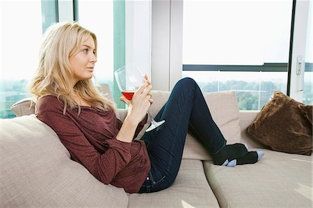 Side view of young woman with wine glass in living room at home Stock Photo - Premium Royalty-Free, Code: 693-07456014