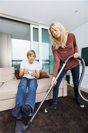 Woman vacuuming while man play video game in living room at home Stock Photo - Premium Royalty-Free, Code: 693-07456044