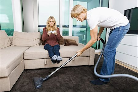 Man vacuuming while woman play video game in living room at home Stock Photo - Premium Royalty-Free, Code: 693-07456045