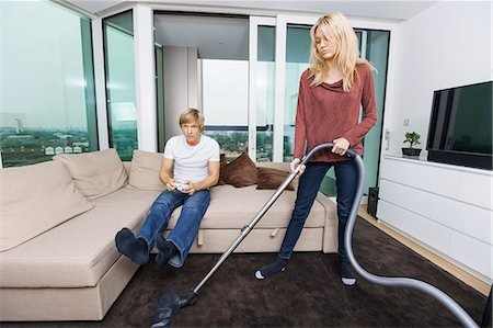 Woman vacuuming while man play video game in living room at home Stock Photo - Premium Royalty-Free, Code: 693-07456042