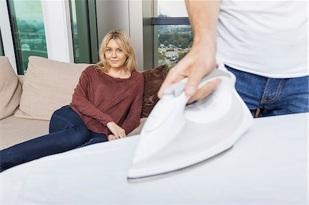 Man ironing shirt while woman relaxing on sofa at home Stock Photo - Premium Royalty-Free, Code: 693-07456050