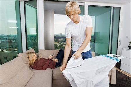 Man ironing shirt while woman relaxing on sofa at home Stock Photo - Premium Royalty-Free, Code: 693-07456052