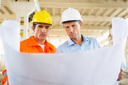 professional (pertains to traditional blue collar careers) - Male architects reviewing blueprint at construction site Stock Photo - Premium Royalty-Free, Code: 693-07456128