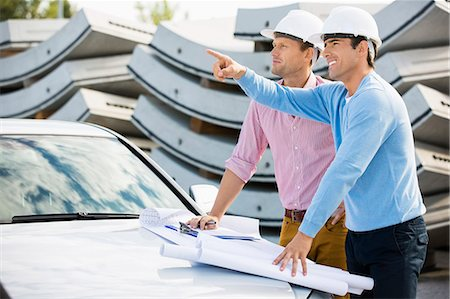 Architects with blueprints on car discussing at site Stock Photo - Premium Royalty-Free, Code: 693-07456138
