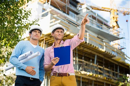 professional (pertains to traditional blue collar careers) - Male architects with blueprint and clipboard working at site Stock Photo - Premium Royalty-Free, Code: 693-07456149