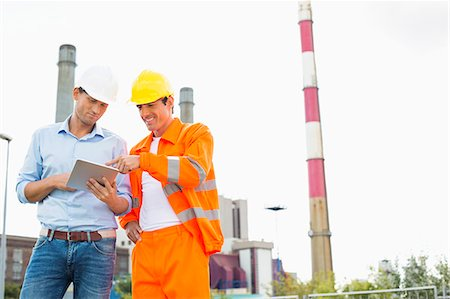 Two construction workers discussing over tablet PC at industry Stock Photo - Premium Royalty-Free, Code: 693-07456182
