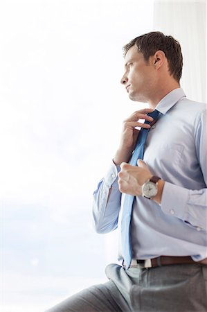 Thoughtful businessman adjusting necktie in hotel Stock Photo - Premium Royalty-Free, Code: 693-07456214