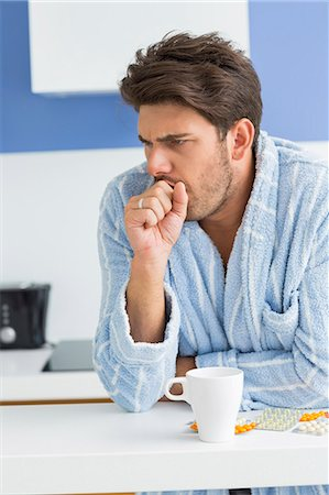 people coughing or sneezing - Young man coughing with coffee mug and medicine on kitchen counter Stock Photo - Premium Royalty-Free, Code: 693-07456340