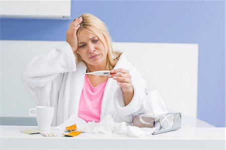 Young woman suffering from cold checking tempereature Stock Photo - Premium Royalty-Free, Code: 693-07456350