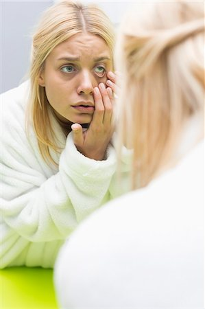Young woman examining eye in mirror Stock Photo - Premium Royalty-Free, Code: 693-07456366