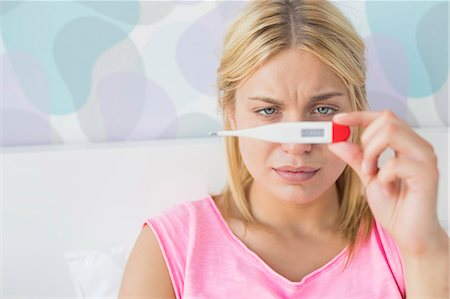 Close-up of sick woman taking temperature with thermometer in bed Stock Photo - Premium Royalty-Free, Code: 693-07456376