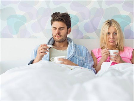 Sad couple holding coffee mugs while relaxing on bed Stock Photo - Premium Royalty-Free, Code: 693-07456386
