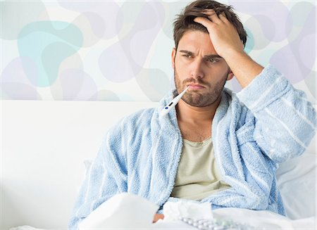 Sick man with thermometer in mouth sitting on bed at home Stock Photo - Premium Royalty-Free, Code: 693-07456407