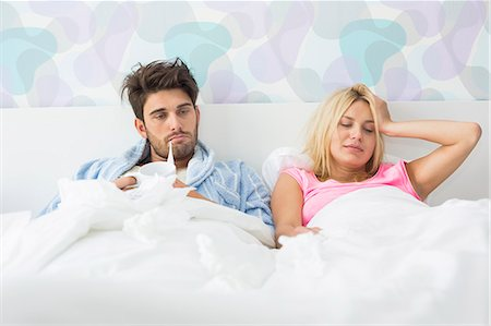 Frustrated sick couple lying in bed at home Stock Photo - Premium Royalty-Free, Code: 693-07456412