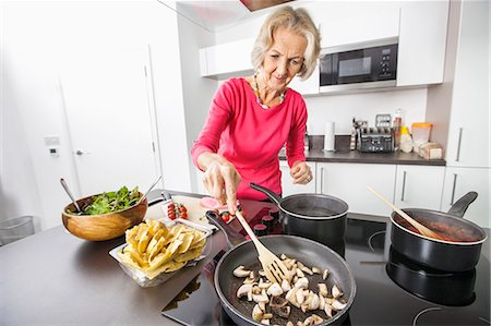 stove - Senior woman cooking food in kitchen Stock Photo - Premium Royalty-Free, Code: 693-07456445