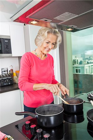 domestic life - Smiling senior woman preparing food at kitchen counter Stock Photo - Premium Royalty-Free, Code: 693-07456446
