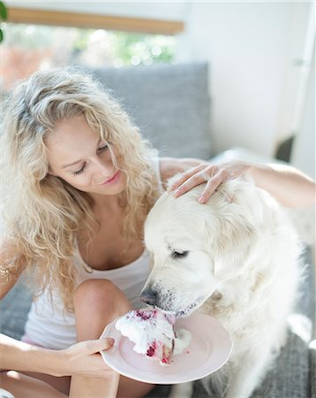 dog and woman and love - Beautiful woman feeding cake to dog in house Stock Photo - Premium Royalty-Free, Code: 693-07542099
