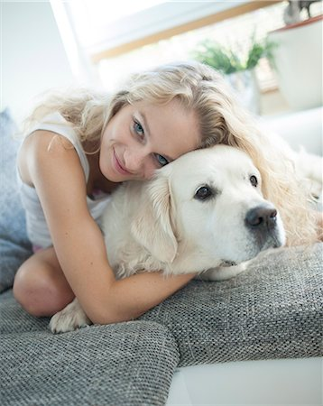 dog and woman and love - Beautiful woman hugging dog on sofa Stock Photo - Premium Royalty-Free, Code: 693-07542104