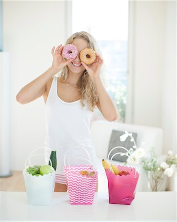 person - Happy woman holding donuts in front of eyes at kitchen counter Stock Photo - Premium Royalty-Free, Code: 693-07542114