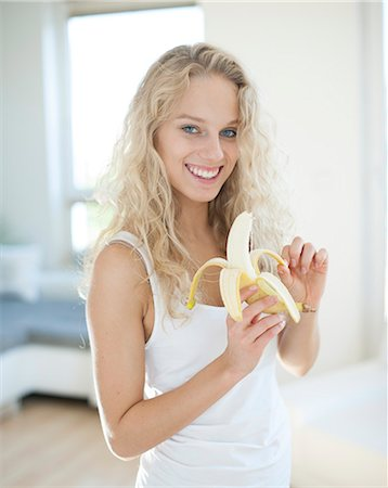 Portrait of young woman peeling banana in house Stock Photo - Premium Royalty-Free, Code: 693-07542116