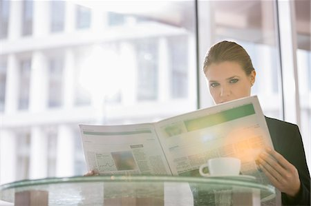 Businesswoman reading newspaper at office cafe Stock Photo - Premium Royalty-Free, Code: 693-07542123