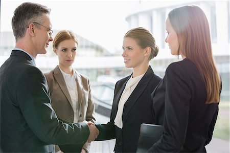 Confident business people shaking hands at workplace Stock Photo - Premium Royalty-Free, Code: 693-07542133