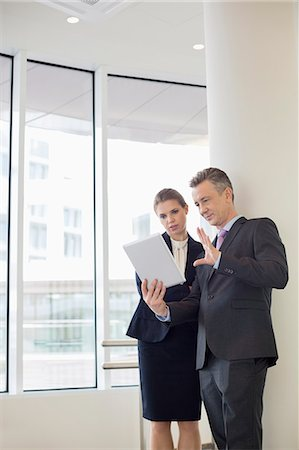 Businessman using digital tablet with female colleague in office Stock Photo - Premium Royalty-Free, Code: 693-07542148
