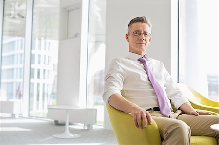 Portrait of confident businessman sitting at office lobby Stock Photo - Premium Royalty-Free, Code: 693-07542157