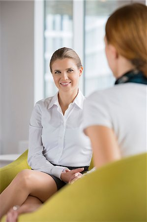 Smiling businesswoman with colleague at lobby Stock Photo - Premium Royalty-Free, Code: 693-07542166