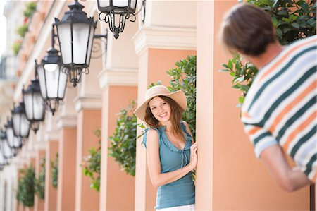 Happy woman playing hide-and-seek with man amongst pillars Stock Photo - Premium Royalty-Free, Code: 693-07542204